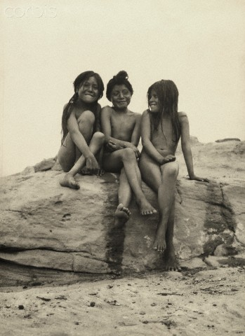Frederick I Monsen - Three naked, Hopi girls sit together on a rock ledge (1921)