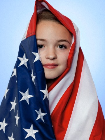 Dustin Todd - Studio portrait of girl (10-11) wrapped in american flag (Date Unknown)