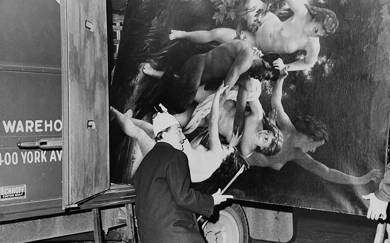 Gamma-Keystone - Salvador Dali helping to load in a truck a copy of the painting Nymphs And Satyr by Bouguereau